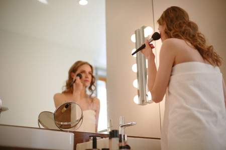 grooming: Young woman looking in the mirror and putting make-up on.