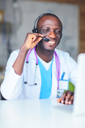 Portrait of young male doctor wearing headset while using comput Stock Photo