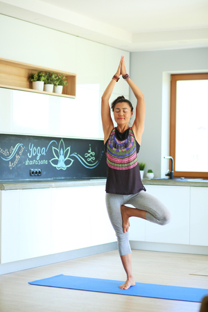 Portrait of smiling yoga woman sitting at yoga mat after workout