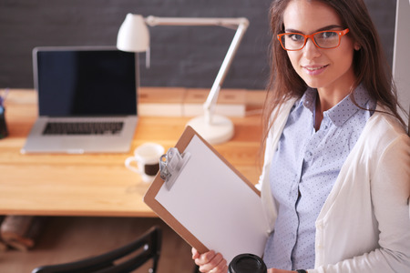 cu: Young woman standing near desk with laptop holding folder and cu