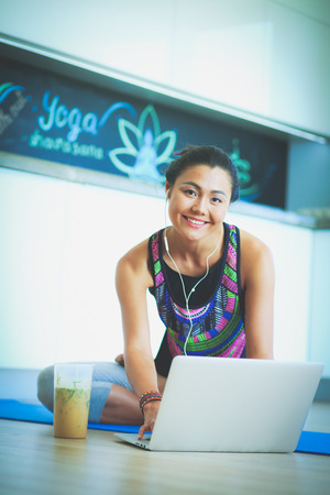 floorboards: Sporty smiling woman using laptop in bright room. Woman. Lifesty