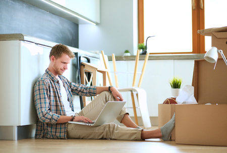 Young man moving in new home.Sitting on floor and relaxing with laptop Stok Fotoğraf - 80884492