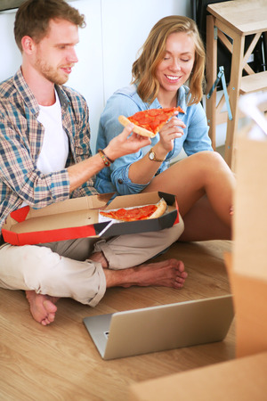 Young couple have a pizza lunch break on the floor after moving into a new home with boxes around them Imagens