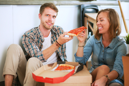 Young couple have a pizza lunch break on the floor after moving into a new home with boxes around them Stock Photo