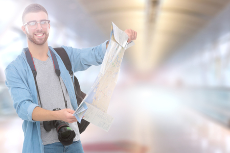 Handsome tourist looking at map standing on street