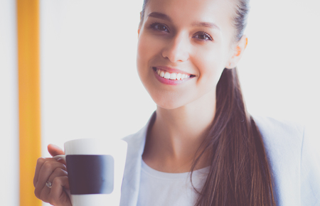 Attractive woman sitting at desk in office, working with laptop , having takeaway coffee Stock Photo