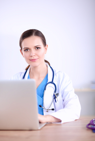 Beautiful young smiling female doctor sitting at the desk and writing Stock Photo