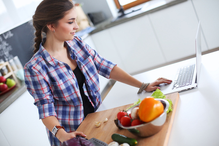Young woman cutting vegetables in kitchen near desk.