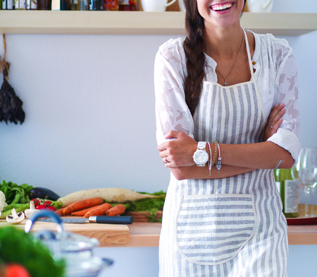 appliances: Young woman standing near desk in the kitchen