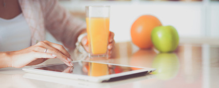 Woman using a tablet computer while drinking juice in her kitchen Stock Photo