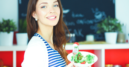 Young woman eating salad and holding a mixed Stock Photo