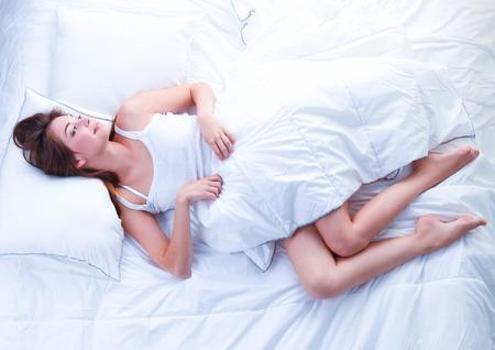 bedroom: Beautiful girl sleeps in the bedroom, lying on bed Stock Photo
