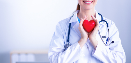 Young woman doctor holding a red heart, isolated on white background Stockfoto