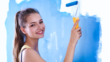 renew.: Happy beautiful young woman doing wall painting, standing on ladder Stock Photo
