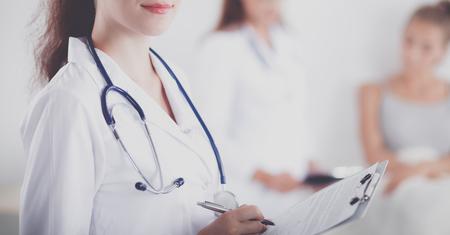 Doctora sonriente con una carpeta en uniforme de pie en el hospital Foto de archivo - 82731569