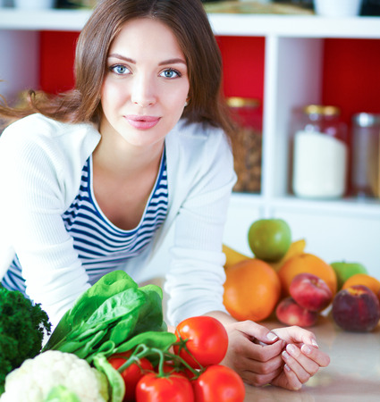 appliances: Young woman sitting near desk in the kitchen Stock Photo