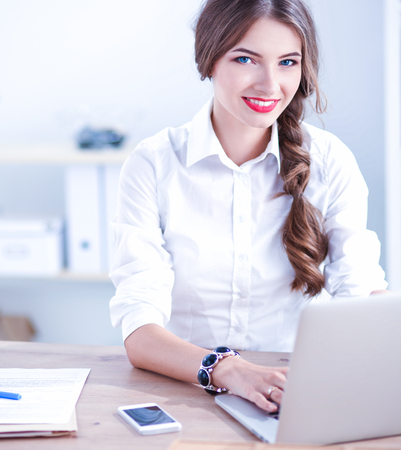 Attractive businesswoman sitting  on desk in the office Stock Photo