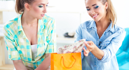 bedroom: Two young women sitting with shopping bag at home
