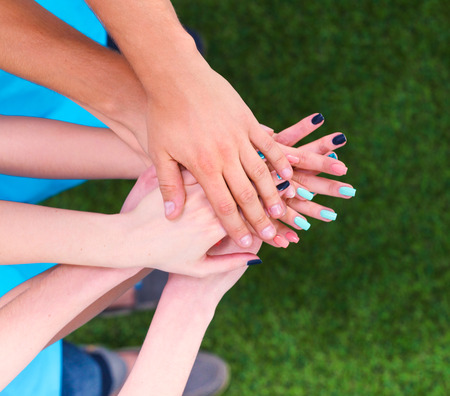 People joining their hands  on green grass . Stock Photo