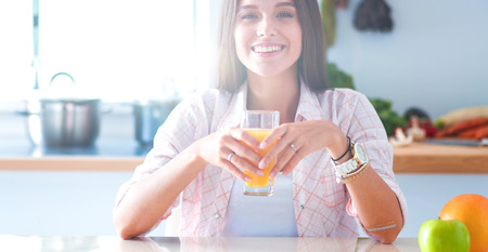 Young woman sitting near desk in the kitchen Stock Photo