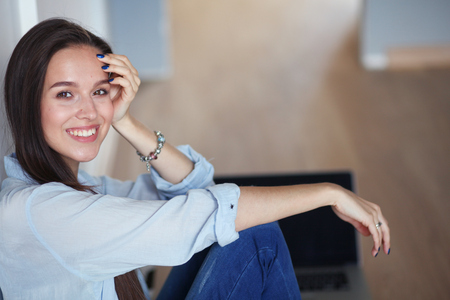 floorboards: Young beautiful woman at home sitting on the floor with laptop. Young beautiful woman. Stock Photo