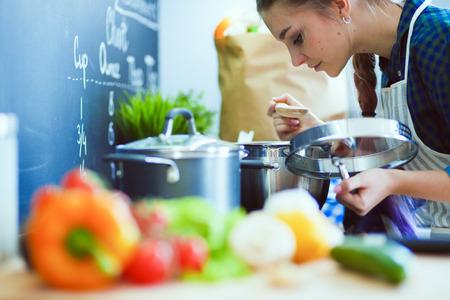 Jonge vrouw die zich bij de kachel in de keuken.