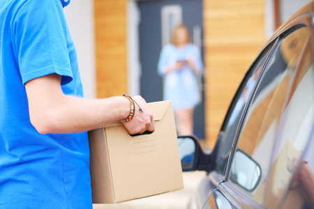 Smiling delivery man in blue uniform delivering parcel box to recipient - courier service concept. Smiling delivery man in blue uniform.