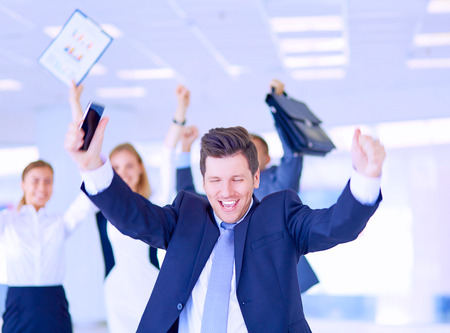 Business team celebrating a triumph with arms up Stock Photo