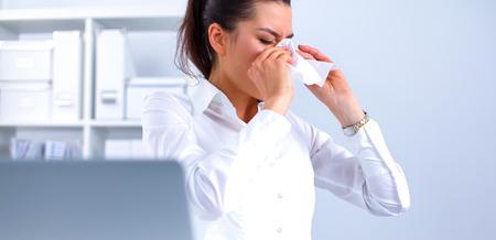 Jonge zakenvrouw blaas haar neus, zit aan de balie