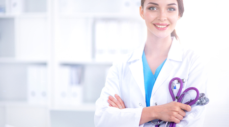 Portrait of happy successful young female doctor holding a stethoscope Stock Photo
