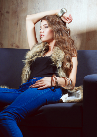 Portrait of elegant woman sitting on black sofa wearing a blue jeans and fur vest Stock Photo