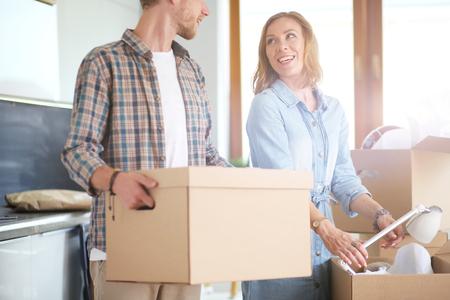 段ボールを開梱カップルは、彼らの新しい家でボックスします。若いカップル。