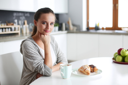 Woman drinking tea with sweet croissant at the kitchen table.