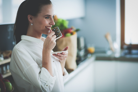 Young beautiful woman drink a coffee at the kitchen.