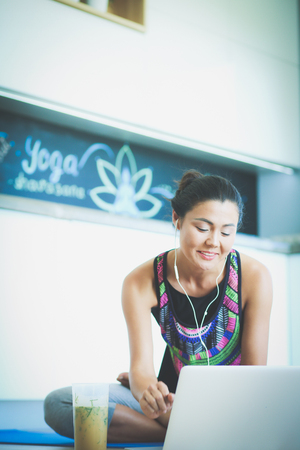 floorboards: Sporty smiling woman using laptop in bright room. Woman. Lifestyle
