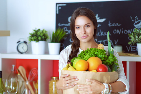 supermarket: Young woman holding grocery shopping bag with vegetables