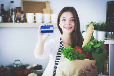 supermarket: Young woman holding grocery shopping bag with vegetables and card