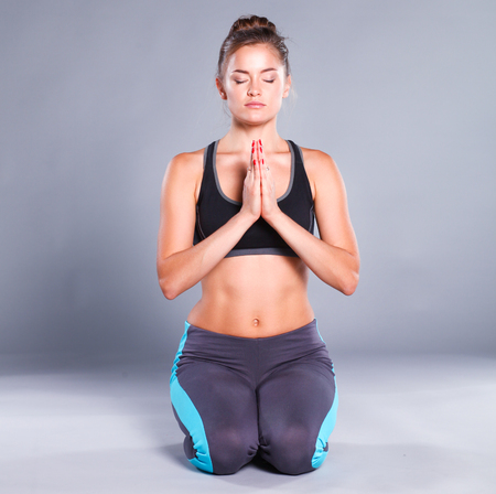 Young woman sitting on the floor in lotus position