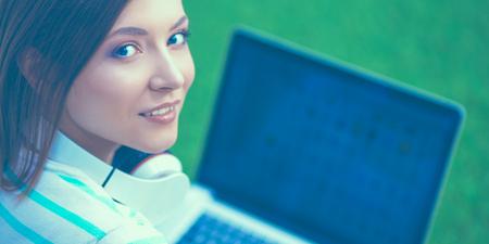 Junge Frau mit dem Laptop, der auf grünem Gras sitzt Standard-Bild - 84854455