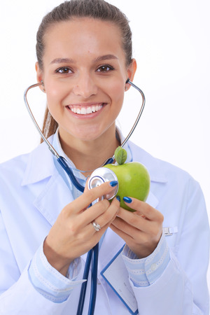 dietetics: Medical doctor woman examining apple with stethoscope. Woman doctors