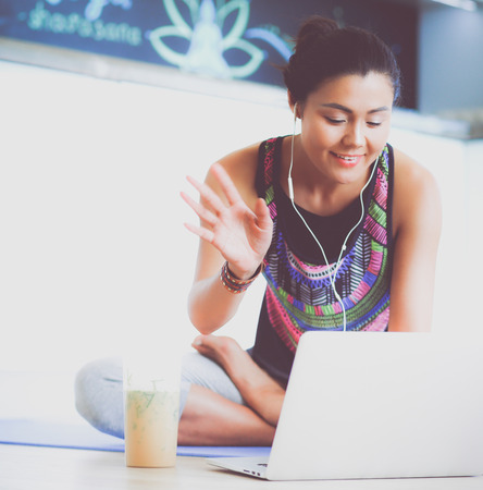 floorboards: Sporty smiling woman using laptop in bright room