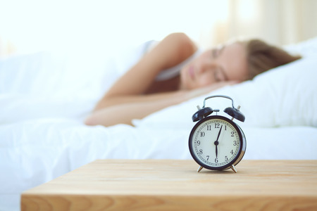 Young sleeping woman and alarm clock in bedroom at home. Young sleeping woman. Stock Photo