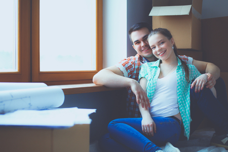 Couple moving in house sitting on the floor. Couple