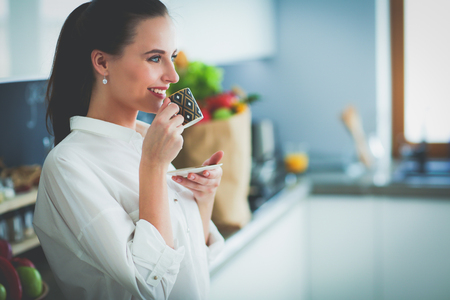 cu: Young woman planning expenses and paying bills on her kitchen.
