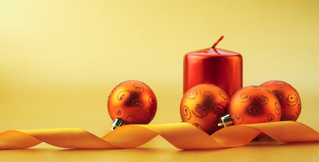 Gold christmas balls and red candle on light background