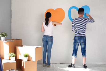 Portrait of happy smiling young couple painting interior wall of new house. young couple Imagens