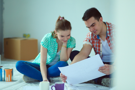 Young couple sitting on floor and calculating about they savings. Young couple Stock Photo