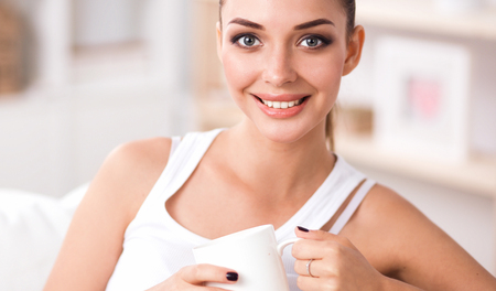 Young beautiful woman with a cup on sofa at home Stock Photo