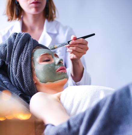 Beautiful woman having mask , lying on spa