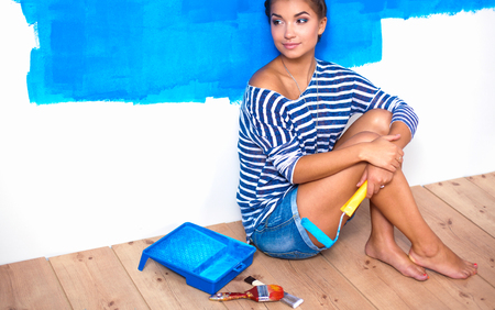 Portrait of female painter sitting on floor after painting Stock Photo